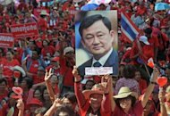 """Red Shirt"" supporters hold a picture of fugitive former premier Thaksin Shinawatra during a demonstration in Bangkok on Saturday to mark the second anniversary of a deadly crackdown on street protests"