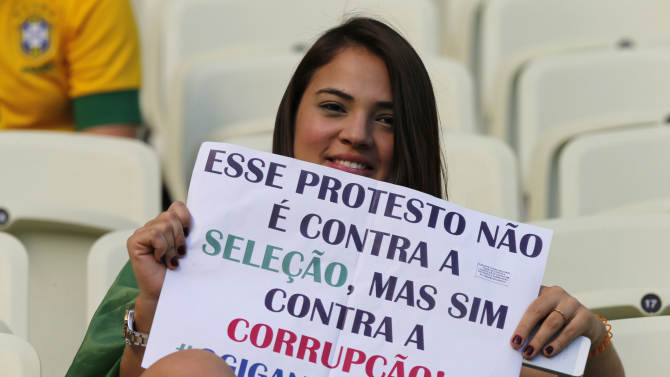 "A woman holds a sign ""This protest is not against our national team but against corruption. The big giant woke up"" prior to the soccer Confederations Cup group A match between Brazil and Mexico at Castelao stadium in Fortaleza, Brazil, Wednesday, June 19, 2013. (AP Photo/Fernando Llano)"