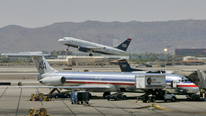 FILE - In this June 23, 2008 file photo, a US Airways jet takes-off as an American Airlines Jet is prepped for takeoff at Sky Harbor International Airport in Phoenix. The parent company of American Airlines has entered a non-disclosure agreement with U.S. Airways that will allow the companies to discuss combining the companies. AMR Corp., which is in Chapter 11 bankruptcy reorganization, and U.S. Airways Group Inc. said Friday, Aug. 31, 2012, that they've agreed not to talk to other parties about any potential combination while they are evaluating their situation with each other. (AP Photo/Matt York, File)