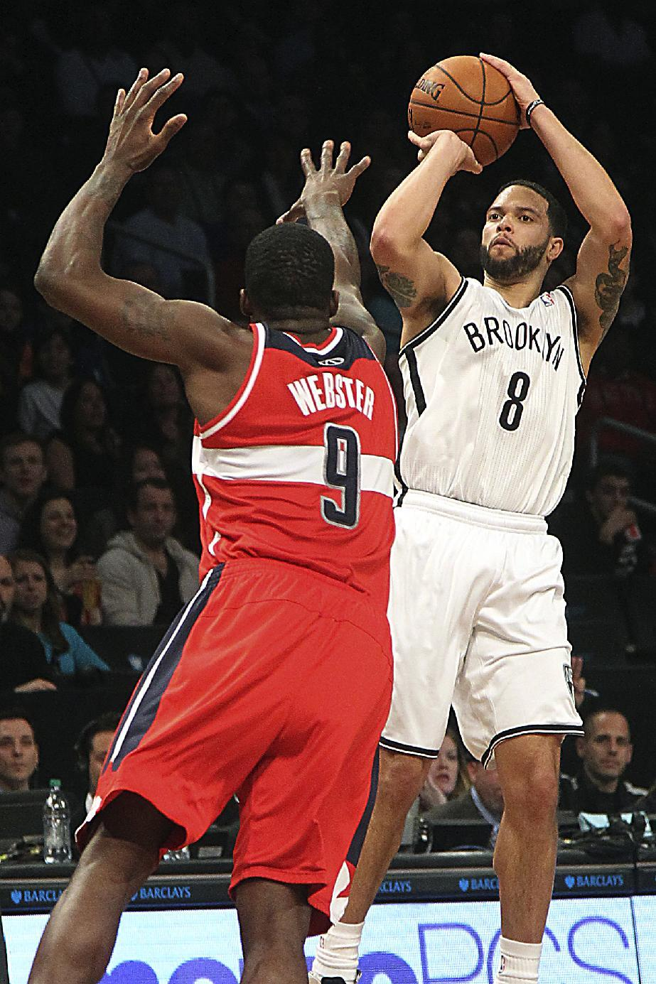 Brooklyn Nets' Deron Williams (8) shoots a 3-pointer past Washington Wizards' Martell Webster during the first half of NBA basketball game, Friday, March 8, 2013, in New York. Williams set the NBA record with nine 3-pointers in a half during the first half of their game. (AP Photo/Mary Altaffer)