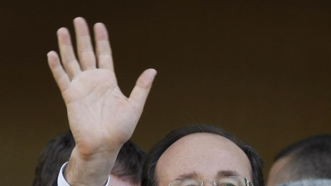 Socialist Party candidate for the presidential election Francois Hollande waves after visiting a polling station near Tulle, central France, Sunday, May 6, 2012.  (AP Photo/Lionel Cironneau)