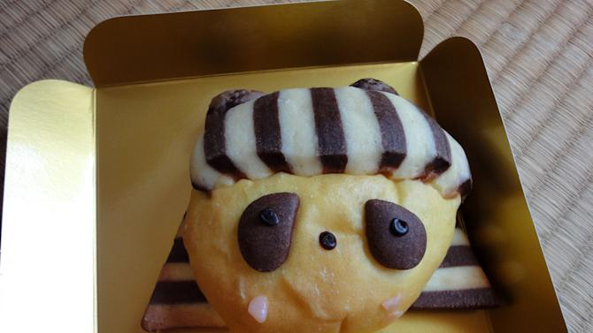 This Sept. 14, 2012 photo shows a bun sold at a bakery in Tokyo's Ueno train station. The bun is designed like a panda, in honor of the panda at Tokyo's Ueno Zoo, and it is wearing an Egyptian headdress in honor of an exhibit at a museum in the same park. (AP Photo/Linda Lombardi)