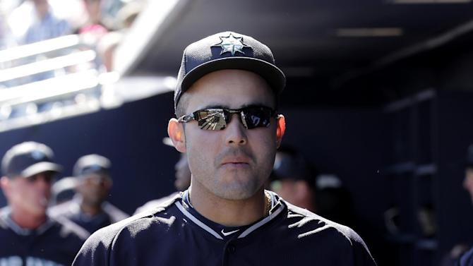 Seattle Mariners' Jesus Montero walks through the dugout before a spring training baseball game against the San Diego Padres Thursday, March 5, 2015, in Peoria, Ariz. (AP Photo/Charlie Riedel)