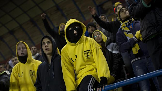 """In this Tuesday, Jan. 29, 2013 photo Beitar Jerusalem F.C. soccer supporters watch a State Cup soccer match against Maccabi Umm al-Fahm F.C. at the Teddy Stadium in Jerusalem. Beitar has long tried to quell a tight-knit group that calls itself """"La Familia"""" and whose behavior has had the team docked points and forced it to play before empty stadiums. The group is routinely abusive toward opposing players, taunting them with racist and anti-Arab chants. (AP Photo/Bernat Armangue) The offices of the Beitar Jerusalem soccer team were set on fire early Friday in an apparent arson attack, police said, a day after four of the club's fans were charged with anti-Muslim chanting at a recent game. Tensions have been bubbling ever since the team announced last month it would sign on two Muslim Chechen players — Zaur Sadayev and Gabriel Kadiev — in a break from the team's unofficial tradition of not signing Arabs or Muslims. (AP Photo/Bernat Armangue)"""
