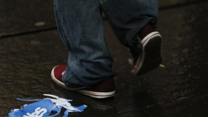 "A man walks past a discarded ""Yes"" campaign paper hat on the Royal Mile after the referendum on Scottish independence in Edinburgh"
