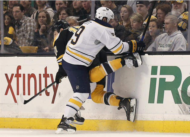 Buffalo Sabres' Steve Ott checks Boston Bruins' Milan Lucic during the first period of an NHL hockey game in Boston, Saturday, Dec. 21, 2013