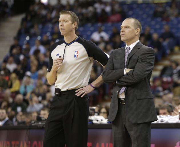 Sacramento Kings head coach Michael Malone,right, talks with Official Ed Malloy during the fourth quarter of the Kings 105-100 loss to the Atlanta Hawks in an NBA basketball game in Sacramento, Calif.