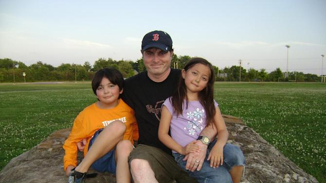 FILE - This June 2009 photo provided by Christopher Savoie shows him, center, with his son, Isaac, and daughter, Rebecca, at a park near their home in Franklin, Tenn.  The children were later taken to Japan by their mother, in violation of a U.S. court custody decision, and Christopher Savoie was arrested in Japan in September 2009 during an unsuccessful attempt to regain custody.  Japan's parliament on Wednesday, May 22, 2013,  approved joining the 1980 Hague Convention on international child abduction amid foreign pressure for Tokyo to address concerns that Japanese mothers can take children away from foreign fathers without recourse.  (AP Photo/Amy Savoie, File)