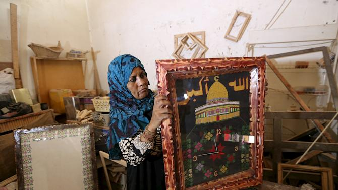 Palestinian carpenter Amal Abu Regaiq, 43, shows a border she designed which frames an embroidery depicting the Dome of the Rock, at her workshop in Nuseirat in the central Gaza Strip