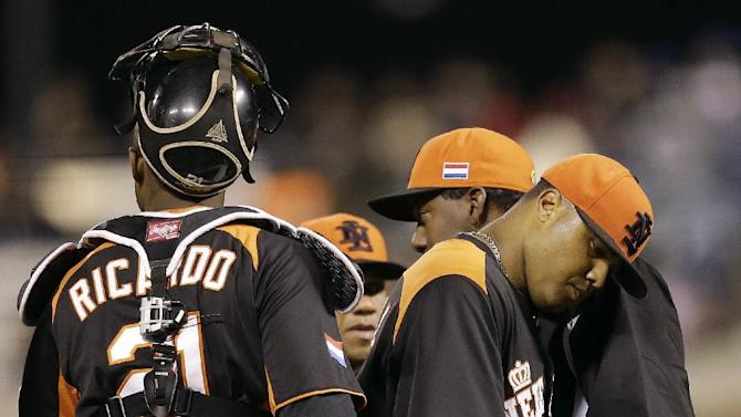 The Netherlands' Diegomar Markwell, second from right, walks off the mound after being relieved by manager Hensley Meulens, right, during the fifth inning of a semifinal game of the World Baseball Classic against the Dominican Republic in San Francisco, Monday, March 18, 2013. Also pictured at left is Dashenko Ricardo. (AP Photo/Ben Margot)