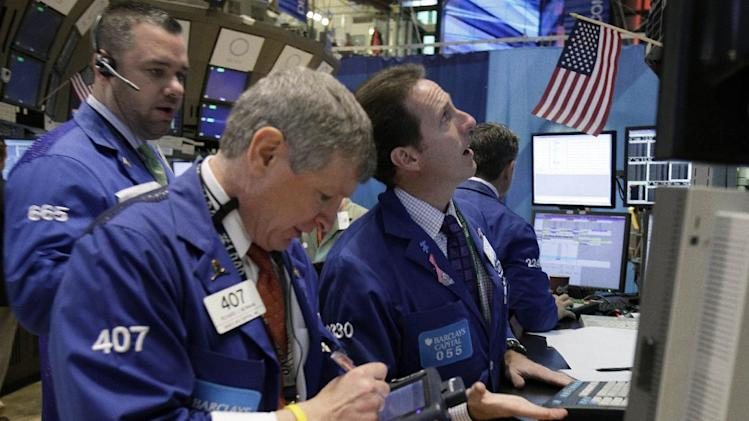 In this Nov. 21, 2011 photo, specialist Glenn Carell, right, works at his post on the floor of the New York Stock Exchange. The collapse of talks aimed at reducing the staggering U.S. budget deficit weighed on world markets Tuesday, Nov. 22, 2011, but failed to stifle a rebound in Europe.(AP Photo/Richard Drew)