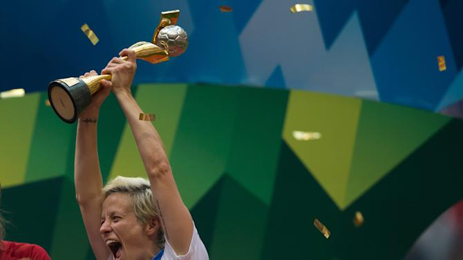 United States' Megan Rapinoe hoists the trophy as she celebrates after defeating Japan to win the FIFA Women's World Cup soccer championship in Vancouver, British Columbia, Canada, Sunday, July 5, 2015.   (Darryl Dyck/The Canadian Press via AP) MANDATORY CREDIT