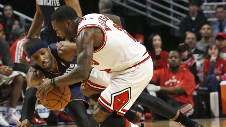 Chicago Bulls guard Nate Robinson (2) works against Charlotte Bobcats forward Hakim Warrick for a loose ball during the first half of an NBA basketball game Monday, Dec. 31, 2012, in Chicago. (AP Photo/Charles Rex Arbogast)