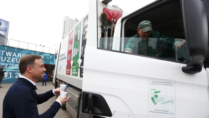 Duda, presidential candidate of the Law and Justice Party (PiS), gives a cup of coffee to a worker in a garbage truck outside a subway station in central Warsaw