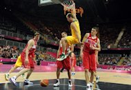 Australian forward Brad Newley (up) scores a basket during the Men's Basketball Preliminary Round match as part of the London 2012 Olympic Games at the Basketball Arena on August 6, 2012 in London, England. Australia won 82-80. AFP PHOTO / MARK RALSTON