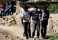 A man who lost his son is supported by others after a 6.6 magnitude earthquake hit Minxian county, Dingxi, Gansu province July 22, 2013. REUTERS/China Daily