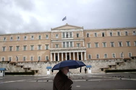 A man holding an umbrella makes his way in front of the Greek parliament during rainfall in Athens