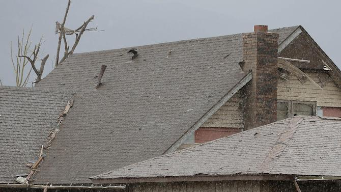 An unidentified man watches a rain storm from inside the garage of his tornado-damaged home Tuesday, May 21, 2013, in Moore, Okla. A huge tornado roared through the Oklahoma City suburb Monday, flattening entire neighborhoods and destroying an elementary school with a direct blow as children and teachers huddled against winds. (AP Photo/Charlie Riedel)