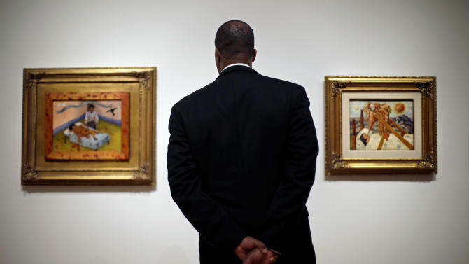 "This Feb. 8, 2013 photo shows Rory Hall, of Atlanta, viewing two paintings by artist Frida Kahlo as part of the exhibition ""Frida & Diego: Passion Politics and Painting,"" featuring the works of Kahlo and Diego Rivera at the High Museum in Atlanta. The exhibit features more than 140 works, making it the largest exhibition of the couple's art ever displayed together. Atlanta's High will be the only U.S. venue for the exhibition, which opens Feb. 14 and runs through May 12. (AP Photo/David Goldman)"