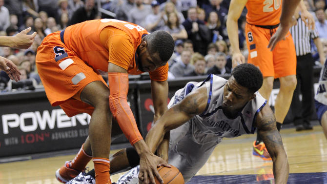 Syracuse forward James Southerland, left, battles for the ball with Georgetown guard D'Vauntes Smith-Rivera, right, during the first half of an NCAA college basketball game, Saturday, March 9, 2013, in Washington. (AP Photo/Nick Wass)