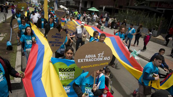 People carry banners and Colombian national flags during a demonstration to demand urgent action to stem climate change, on September 21, 2014 in Bogota