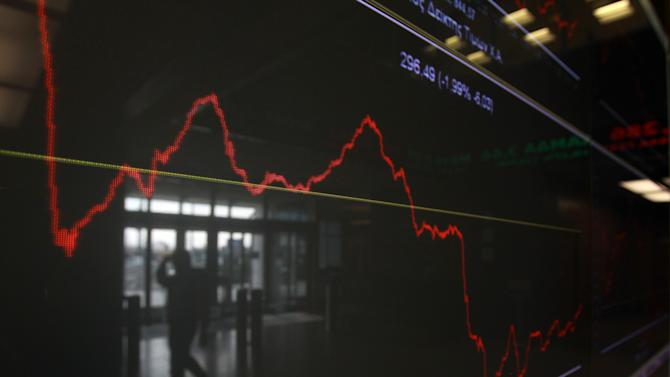 An employee of the Stock Exchange is reflected in a chart displaying stock prices in Athens, Tuesday, Nov. 27, 2012. Greece has avoided imminent bankruptcy after its international creditors finally agreed to give it the money it urgently needs, but the cash-strapped country's economic distress is likely to drag on for years to come. (AP Photo/Thanassis Stavrakis)