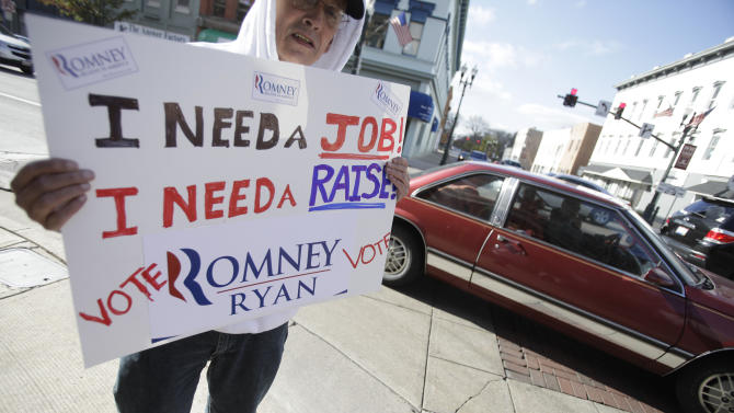 John DeNoyelles, from Flint, Texas, who said he is in Ohio trying to network to find a job, holds a sign in support of Mitt Romney along Main Street in Bowling Green, Ohio Monday Nov. 5, 2012.  (AP Photo/J.D. Pooley)
