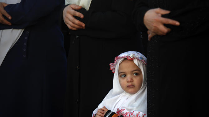 A young Palestinian girl attends prayers on the first day of Eid al-Adha at Al-Yarmouk stadium in Gaza City, Tuesday, Oct. 15, 2013. Muslims worldwide are celebrating Eid al-Adha, or the Feast of the Sacrifice on Oct. 15, by sacrificial killing of sheep, goats, cows or camels. The slaughter commemorates the biblical story of Abraham, who was on the verge of sacrificing his son to obey God's command, when God interceded by substituting a ram in the child's place. (AP Photo/Hatem Moussa)