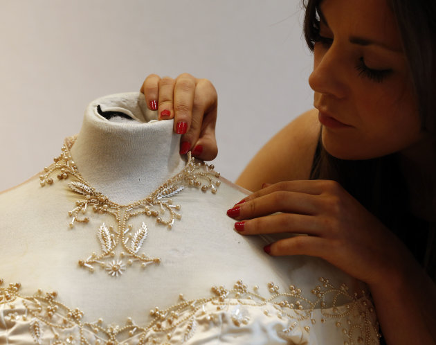 A Christie's employee adjusts Elizabeth Taylor's first wedding dress, designed by the legendary costume designer Helen Rose, at the auction house Chriestie's in London, Wednesday, June 19, 2013. The w