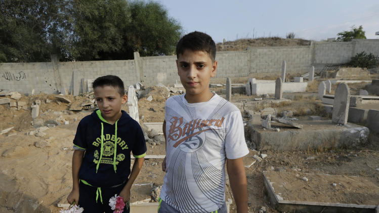 Palestinians Mohammed Afana, 13, right, and Saeb Afana, 12, left, carry flowers as they arrive at a cemetery in Gaza City, in the northern Gaza Strip, Monday, July 28, 2014, to visit the grave of a relative, Ayman Afana, 24, who had been killed in an airstrike in the Sheik Radwan neighborhood some 10 days ago. Monday marked the beginning of the three-day Eid al-Fitr holiday, which caps the Muslim fasting month of Ramadan. Muslims usually start the day by visiting cemeteries, to pay their respects to the dead, and then exchange family visits. (AP Photo/Lefteris Pitarakis)