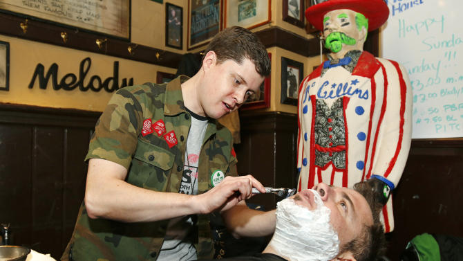 """A barber gives a shave to a pub customer during the Gillette """"Kiss Me, I'm Smooth Shaven!"""" festivities at McGillin's Ale House, reminding guys to K.I.S.S. - Keep It Smooth Shaven - on Sunday, March 10, 2013 in Philadelphia. A recent study revealed that 85% of women prefer to kiss a man who is smooth shaven, and that two out of three women said men will have better luck with them if they are stubble-free. (Photo by Mark Stehle/Invision for Gillette/AP Images)"""
