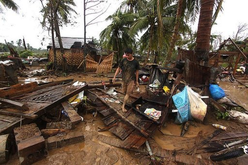 Residents walk among destroyed houses after Typhoon Bopha hit Compostela town, on the southern island of Mindanao on December 4, 2012. The death toll from the typhoon has risen to 82, with 21 people missing, Philippines Interior Minister Mar Roxas said Wednesday after the storm battered the south of the country.
