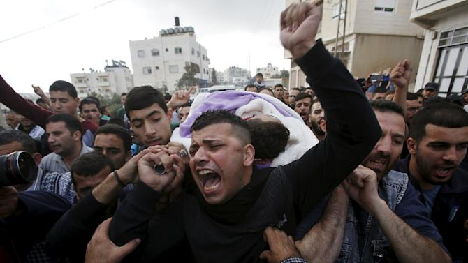 Mourners carry the body of Palestinian Mohammed Jabari, who stabbed an Israeli policeman before being shot dead on Friday, in the West Bank city of Hebron
