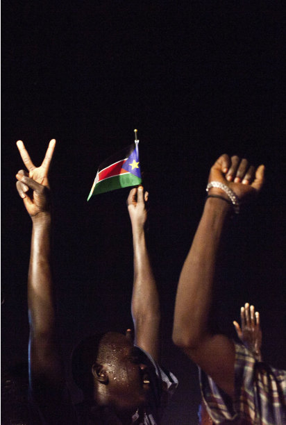 People raise their hands and wave a South Sudan flag in celebration of the country's independence in Juba, South Sudan, late Friday, July 8, 2011. South Sudan became the world's newest nation early Saturday, officially breaking away from Sudan after two civil wars over five decades that cost the lives of millions. (AP Photo/Andrew Burton)