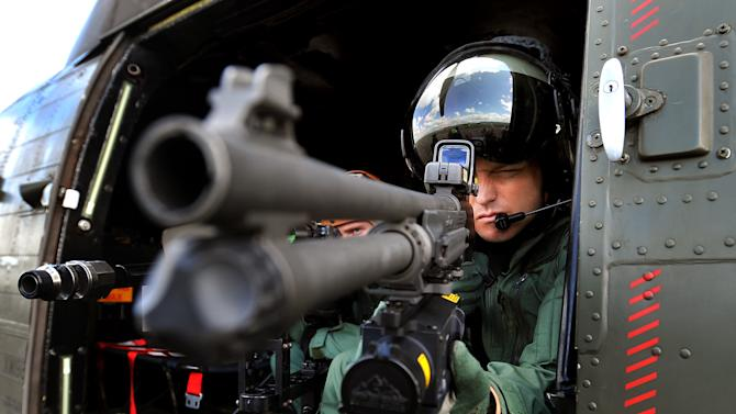 """A sniper with the Royal Air Force Regiment, looks through the scope of his sniper rifle as the military prepares for duty to provide security aboard helicopters high above the London Olympic games, at RAF Northolt, in London, Friday July 13, 2012. Aircraft that fail to comply with procedures within a restricted airspace zone around the Olympic venues could be subject to """"lethal force"""" from the military, it is revealed Friday. RAF Typhoon fast jets and RAF Puma helicopters with snipers armed with hi-tech rifles will be among the military aircraft patrolling the restricted zone which comes into force during the London 2012 Olympic Games. (AP Photo/John Stillwell, PA) UNITED KINGDOM OUT - NO SALES - NO ARCHIVE"""