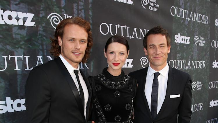 "Sam Heughan, and from left, Caitriona Balf and Tobias Menzies arrive at the premiere for the STARZ original series ""Outlander"" during San Diego Comic-Con on Friday, July 25, 2014 in San Diego. ""Outlander"" premieres on STARZ August 9, 2014. (Photo by Matt Sayles/Invision for STARZ/AP Images)"