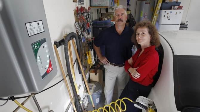Connie and Travis Jones pose with their 2003 natural gas powered Honda Civic and home refueling station at their home in Chandler