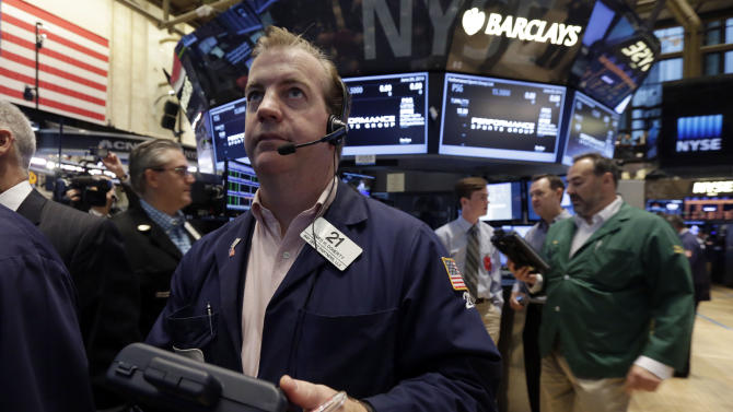 FILE - In this June 20, 2014 file photo, trader James Doherty center, works on the floor of the New York Stock Exchange. In a world suddenly more dangerous, you'd think fund managers and traders would be selling and buying and selling again in a frenzy of second guessing. Instead, they're the picture of calm and contentment. The lack of fear is spooking some people. (AP Photo/Richard Drew, File)
