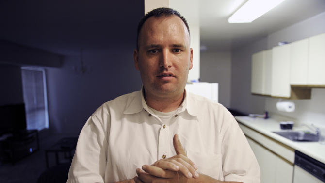 In this Aug. 23, 2012 photo, Kevin Earley, 33, stands between lit and dark rooms in his Vienna, Va., apartment that he shares with a roommate. Earley, who suffers with a mental health condition, works full time as a peer counselor in Fairfax County, Va., helping others with severe mental illnesses. (AP Photo/Cliff Owen)