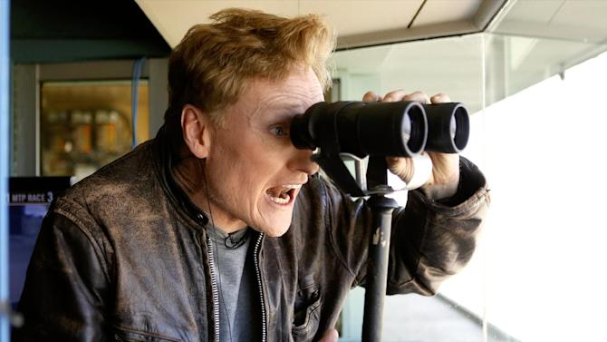 """Television host Conan O'Brien comments on the binoculars of long-time track announcer Trevor Denman, after O'Brien called a horse race at Santa Anita Park, the host track for next month's Breeders' Cup, the richest event in thoroughbred racing in Arcadia, Calif., Friday, Oct. 25, 2013. O'Brien hosts """"Conan"""" weeknights on TBS. (AP Photo/Damian Dovarganes)"""