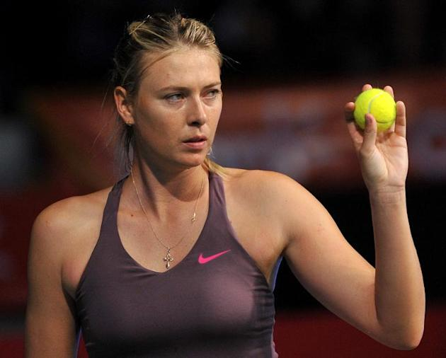 Russian tennis player Maria Sharapova serves a ball to Serbian Ana Ivanovic during an exhibition match in Bogota, Colombia, on December 6, 2013