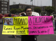 "A man holds up a sign with details of his recently disappeared relative during a protest in Mexico City, Thursday, May 30, 2013. Eleven young people were kidnapped in broad daylight from a Mexico City bar, just 20 days after the grandson of civil rights leader Malcolm X was beaten to death at a nightclub in the capital, anguished relatives said Thursday. The sign reads in Spanish ""Help us find him. Rafael Rojas Marines. Disappeared in the after-hours Heaven. Asking for your support!"" The mother of one of the missing youths says 11 people in all vanished from the after-hours club about 1 ½ blocks from the U.S. embassy, on the other side of Reforma Avenue. (AP Photo/Eduardo Verdugo)"
