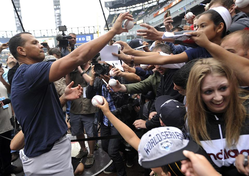 New York Yankees' Alex Rodriguez, left, signs autographs at U.S. Cellular Field before a baseball game against the Chicago White Sox in Chicago, Monday, Aug. 5, 2013. (AP Photo/Paul Beaty)