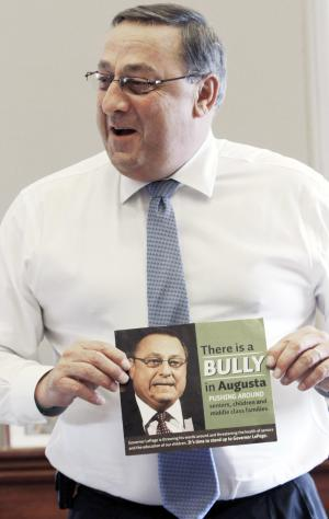 "In this Friday, April 27, 2012 photo, Gov. Paul LePage talks about his sense of humor while holding a poster that reads ""There is a bully in Augusta pushing around seniors, children and middle class families,"" during an interview with the Associated Press at his office at the State House in Augusta, Maine. Critics are putting pressure on LePage to apologize for referring to the Internal Revenue Service as ""the new Gestapo"" during his radio address Saturday, July 7, 2012. (AP Photo/Pat Wellenbach)"