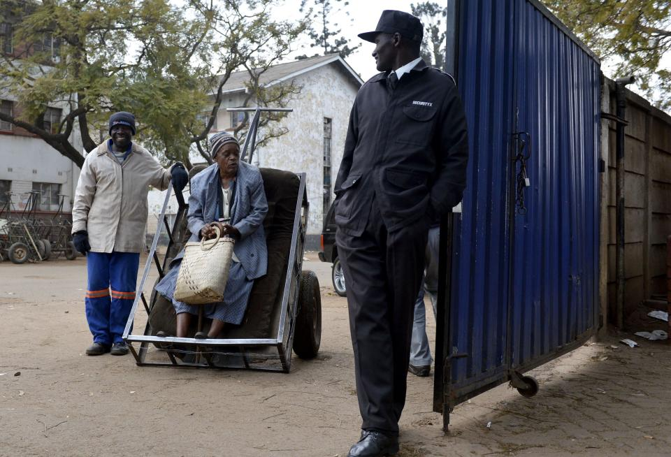A woman voter is brought to a polling station to cast her ballot in elections in Mbare, Harare, early Wednesday July 31, 2013. Zimbabweans voted Wednesday in the elections that will determine the future of longtime President Robert Mugabe, who has denied allegations of vote-rigging despite concerns about the credibility of the polls. (AP Photo)