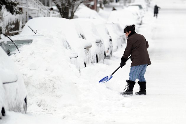 Tina Khoshaboo clears snow from her car on South Water Street during the aftermath of a blizzard in the Byram section of Greenwich, Conn., Saturday morning, Feb. 9, 2013. (AP Photo/Greenwich Time, Bob