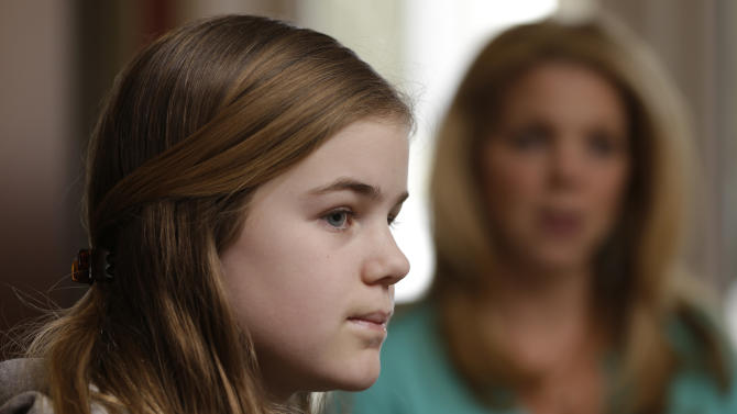 "Caroline Pla, 11, accompanied by her mother Marycecelia ""Seal"" Pla, listens to a question during an interview Thursday, Feb. 21, 2013, in Doylestown, Pa. The Plas are fighting the Roman Catholic Archdiocese of Philadelphia for the right to continue playing church sponsored youth football. (AP Photo/Matt Rourke)"