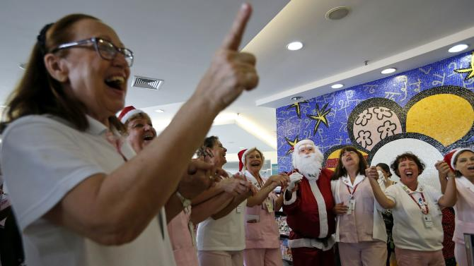 A man dressed as Santa Claus dances with nurses at the Cancer Institute in Sao Paulo