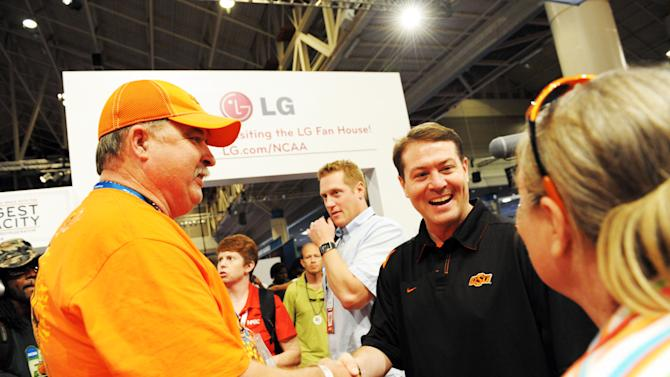 COMMERCIAL IMAGE - In this photograph taken by AP Images for LG Electronics, Oklahoma State University Coach and former University of Kentucky all-star Travis Ford greets fans at the LG House during the NCAA Final Four weekend at Bracket Town at the Ernest N. Morial Convention Center in New Orleans on Sunday, April 1, 2012.  Former NCAA players and current coaches Bobby Hurley and Travis Ford competed in the LG Home Court Challenge, reheating the Duke vs. Kentucky rivalry from 20 years ago. (Cheryl Gerber/AP Images for LG Electronics)