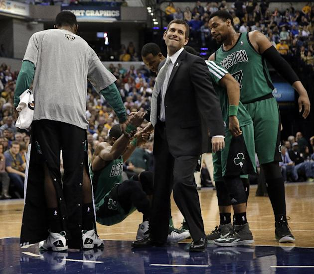 Boston Celtics coach Brad Stevens, center, and members of his team help guard Rajon Rondo up off the floor during the second half of an NBA basketball game against the Indiana Pacers in Indianapolis,